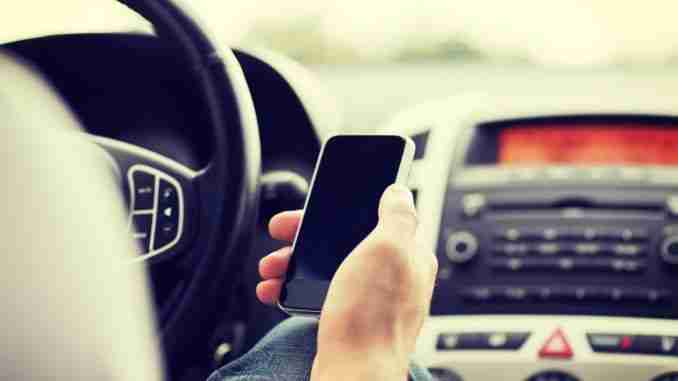 transportation and vehicle concept – man using phone while drivi